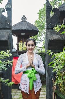 Balinesische frau mit traditioneller kleidung und willkommensgesten smi