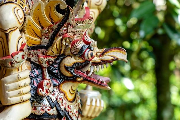 Balinesischer alter bunter vogelgott garuda mit flügeln, nahaufnahme. religiöse traditionelle statue aus holz. alte geschwungene holzfigur des hinduistischen gottes auf der insel bali, ubud, indonesien