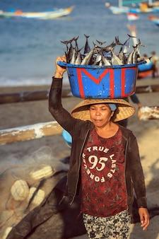 Balinesischer fischhändler tragen fische im becken am morgenmarkt in kedonganan - passant ikan, jimbaran-strand