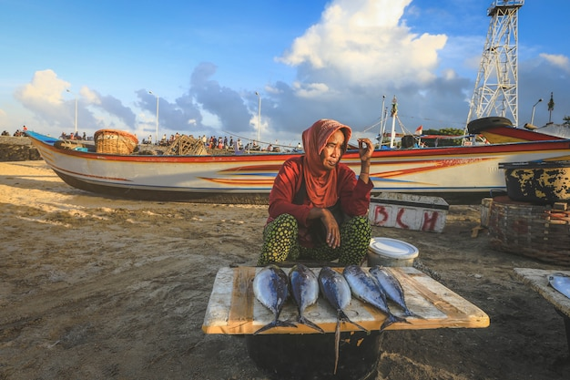 Balinesischer fischhändler verkauft morgens fischmarkt in kedonganan - passant ikan, jimbaran strand