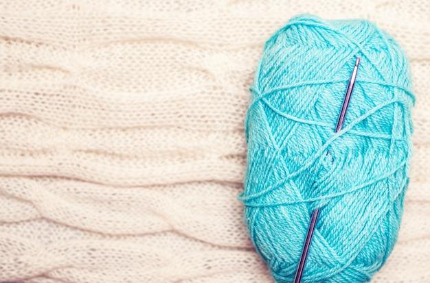 Ball aus blauem garn mit häkelnadel