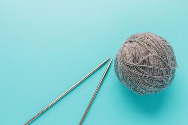 Ball aus grauem wollgarn und metallstricknadeln auf hellblauem hintergrund. strick-, handarbeits- und hobbykonzept. flache lage, draufsicht mit kopierraum.