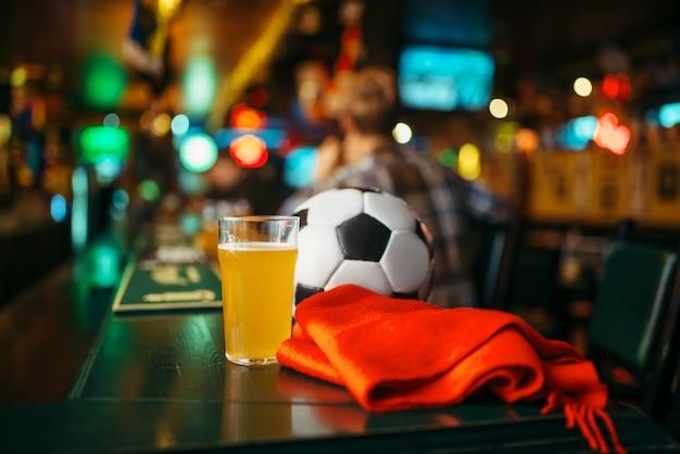 Ball, bier und roter schal auf der theke in der sportbar, fußballfans lebensstil. tv-übertragung, das spielkonzept beobachten