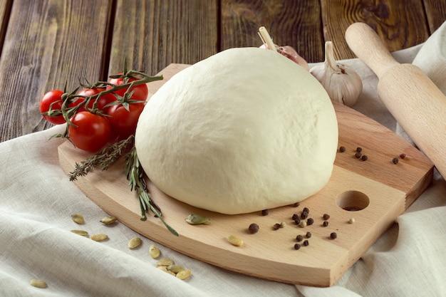 Ball des pizzateigs auf einem rustikalen holz