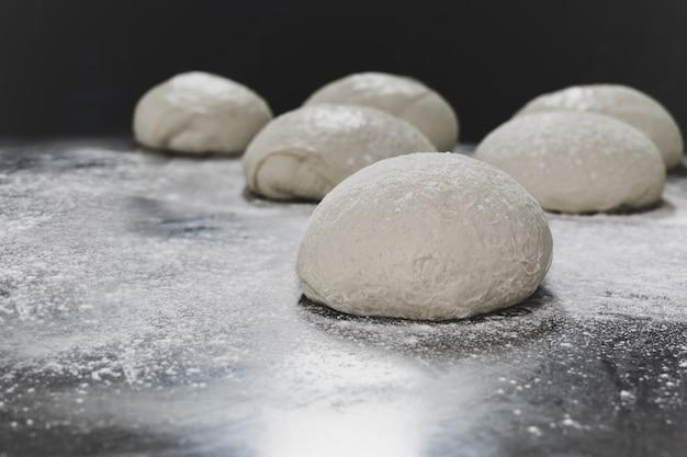 Ball des pizzateigs auf tabelle mit dem abstauben des mehls.