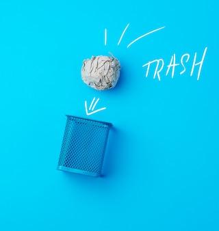 Ball des zerknitterten grauen papiers und des metallblauen papierkorbs
