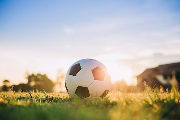 Ball für fußball unter dem sonnenuntergangstrahlnlicht