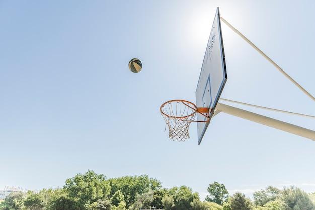 Ball in der luft über dem basketballkorb gegen blauen himmel