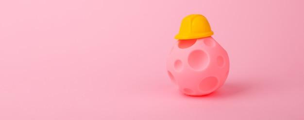 Ball mit kratern im helm über rosa hintergrund, konzept des wohnungsbaus für vertriebene, panorama-modell