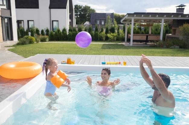 Ball spielen. mädchen mit schönem badeanzug, das sich glücklich fühlt, während sie mit den eltern im pool ball spielt ball