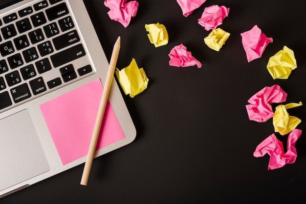 Ball von zerknitterten papieren mit anhaftender anmerkung und bleistift auf laptop gegen schwarzen hintergrund