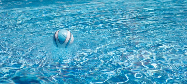 Ball zum spielen im pool in klarem, blauem wasser