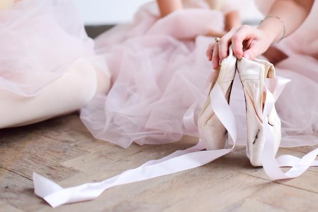 Baller tänzer hält spitzenschuhe
