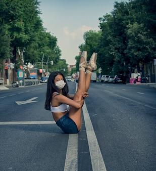 Ballerina auf der straße mit spitzenschuhen und maske