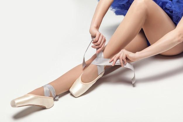 Ballerina binden spitzenschuhe im sitzen isoliert auf weißem studiohintergrund closeup