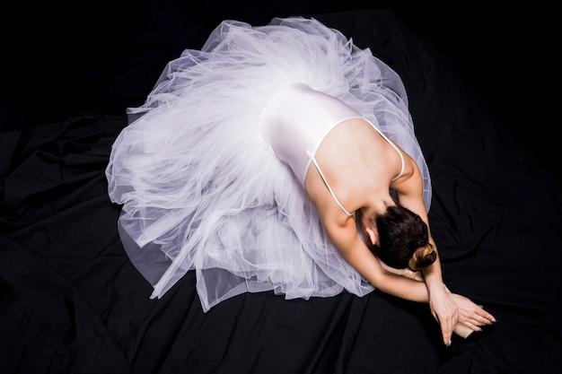 Ballerina des hohen winkels auf dunklem hintergrund