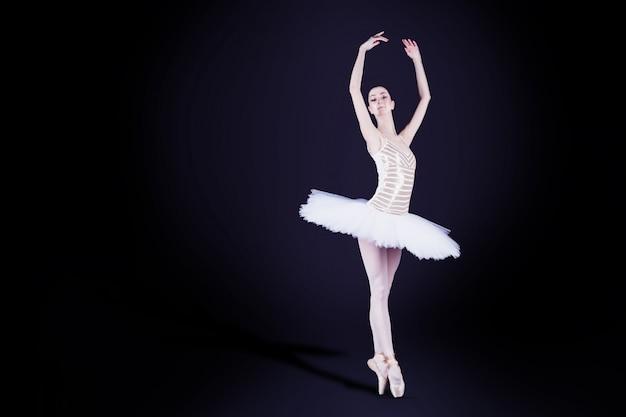 Ballerina des jungen mädchens mit dem tutusolotanzen und -handeln stehen auf zehen in der szene des dunklen schwarzen mit reflektierendem boden