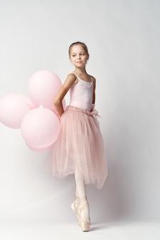 Ballerina des kleinen mädchens in einem weißen anzug in spitzenschuhen