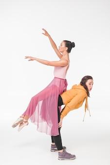 Ballerina, die auf der rückseite der frau über dem weißen hintergrund sitzt
