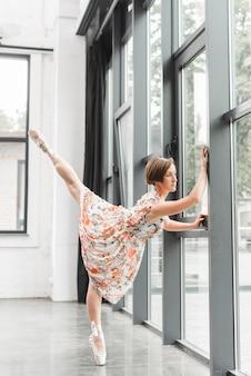 Ballerina, die aufstellung nahe der geschlossenen tür ausdehnt