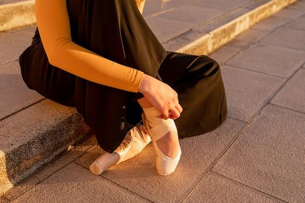 Ballerina, die ballettschuhe mit sonnenuntergangslicht anzieht