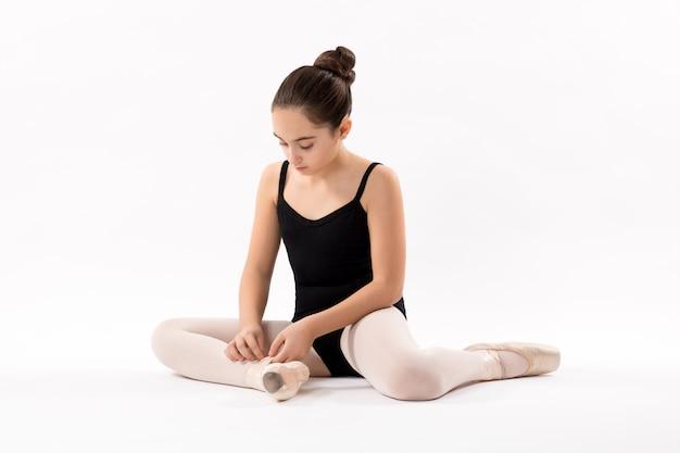 Ballerina, die die schnürsenkel an ihren ballettschuhen bindet