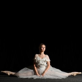 Ballerina, die im ballettröckchenkleid aufwirft und eine spaltung tut