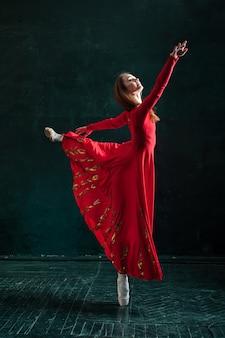 Ballerina, die in spitzenschuhen am schwarzen hölzernen pavillon aufwirft