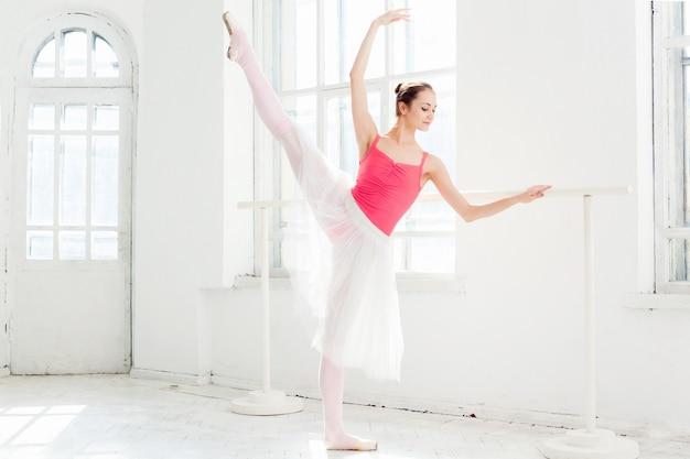 Ballerina, die in spitzenschuhen am weißen hölzernen pavillon aufwirft