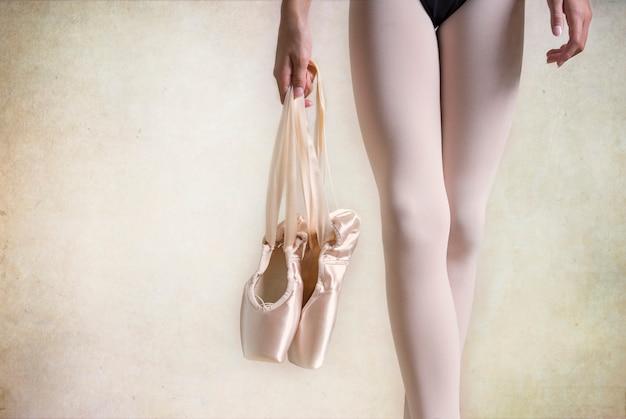Ballerina hält punktschuhe. beine nahaufnahme