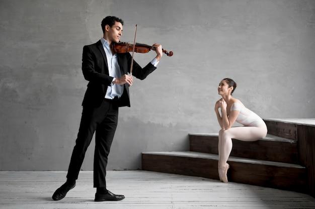 Ballerina hört dem männlichen musiker zu, der geige spielt