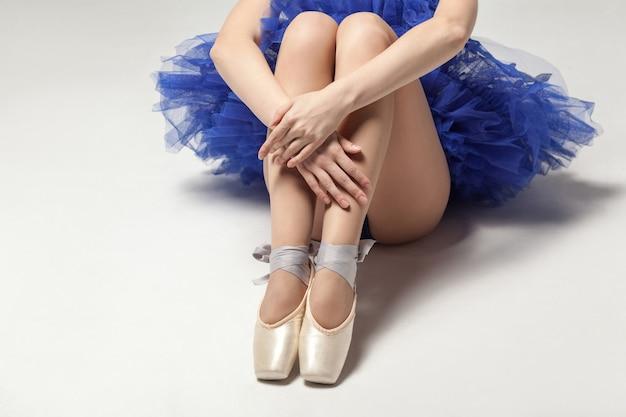Ballerina im blauen kleid und spitzenschuhen, die auf weißem bodennahaufnahme sitzen