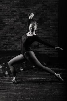 Ballerina im dunklen body, im kleid im dunklen interieur studio. mauer aus ziegeln, klavier.