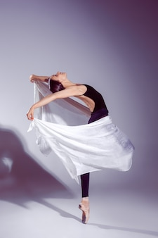 Ballerina im schwarzen outfit posiert auf zehen.