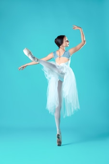 Ballerina im weißen kleid, das auf zehen aufwirft