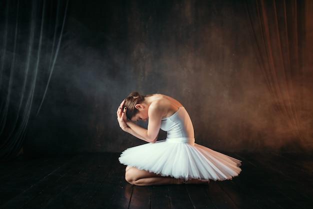 Ballerina im weißen kleid sitzt auf theaterbühne, seitenansicht. klassische balletttänzerausbildung in der klasse auf schwarz