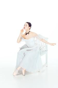 Ballerina im weißen kleid sitzt auf weißem stuhl, studio weiß.