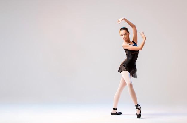 Ballerina in den schwarzen punkten, die in einer anmutigen haltung auf einem weißen hintergrund aufwerfen