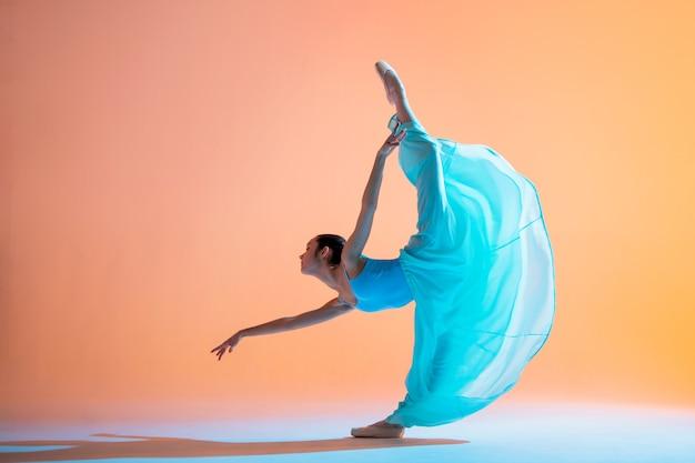 Ballerina in einem hellblauen kleid tanzt auf einem farbigen hintergrund mit rosa hintergrundbeleuchtung
