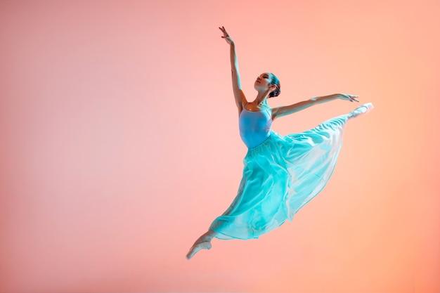 Ballerina in einem hellen hellen kleid, das in einem sprung auf einem beleuchteten farbigen hintergrund fliegt