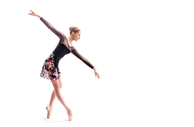 Ballerina in einem hellen kleid tanzt auf einem farbigen hintergrund mit hintergrundbeleuchtung