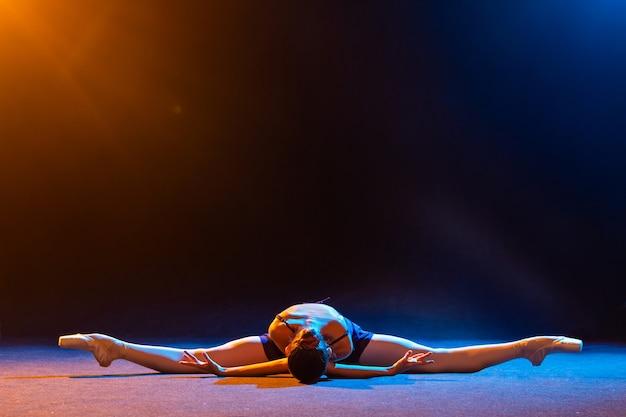 Ballerina in einem schwarzen kleid liegt in einer schnur an einer schwarzen wand, die von bunten scheinwerfern beleuchtet wird