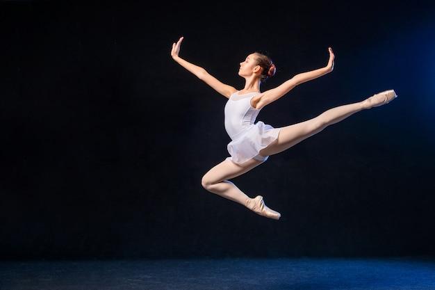 Ballerina in einem weißen kleid fliegt in einem sprung auf einer schwarzen wand