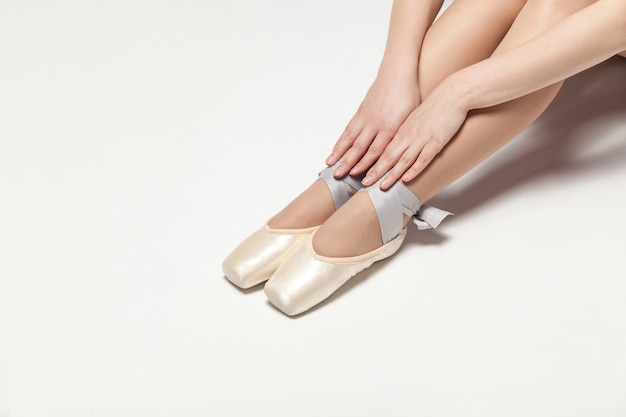 Ballerina in spitzenschuhen sitzt auf weißem boden, nahaufnahme. innen, studioaufnahme.