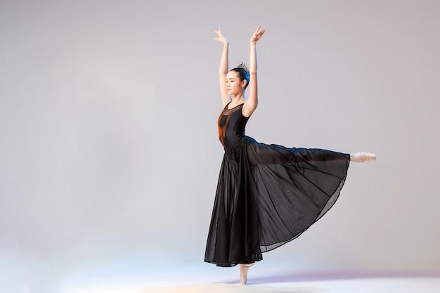 Ballerina in spitzenschuhen und einem langen schwarzen kleid, das auf einer weißen wand tanzt
