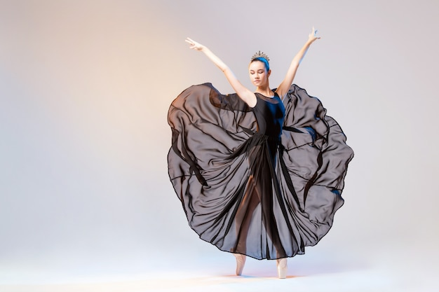 Ballerina in spitzenschuhen und einem langen schwarzen transparenten kleid, das auf einer weißen wand tanzt