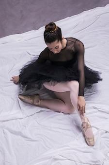 Ballerina mit spitzenschuhen sitzend