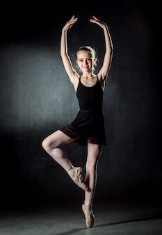 Ballerina. nettes kleines mädchen, das auf der bühne aufwirft und tanzt. das mädchen studiert ballett. .