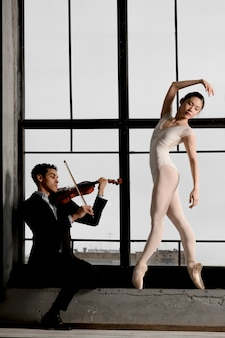 Ballerina posiert, während geiger musik spielt