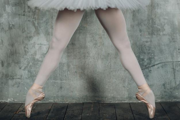 Ballerina schöne beine. junge schöne frau balletttänzerin, gekleidet in professionelles outfit, spitzenschuhe und weißes tutu.
